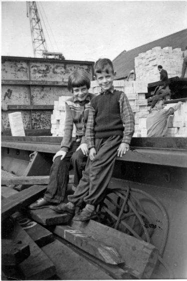 5. With my twin sister Lenie in St Peterport, Guernsey aboard Gerry-S unloding boardbox on August 18, 1956. | Willem Moojen
